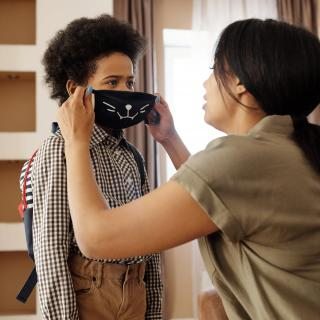 woman putting mask on son